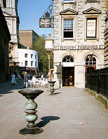"Two ornate metal pillars with large dishes on top in a paved street, with an eighteenth-century stone building behind, upon which can be seen the words ""Tea Blenders Estabklishec 177-"". People sitting at cafe-style tables outside. On the right iron railings."