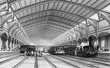 Two trains and two empty rail tracks below an ornate roof which recedes into the distance