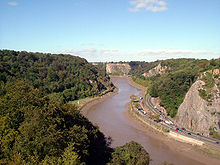 River flowing through gorge with wooded sides. On the right hand bank is a road.