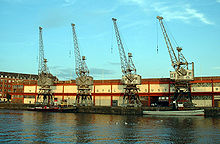 A long two storey building with 4 cranes in front on the quayside. Two tugboats are moored at the quay.