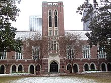 A wide, red brick building with a tower in the center and grey concrete archways spaced along the length of the building.