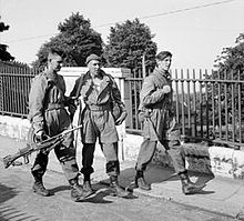 Three men carrying weapons, walking on a pavement with metal railings behind them