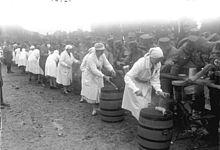 Photo en noir et blanc de sœurs samaritaines en tablier et coiffe blanc, servant à la louche dans la gamelle de soldats placés de l'autre côté d'une barrière, la nourriture qui se trouve dans un tonneau à côté de chacune d'entre elles.