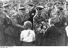 Photographie montrant deux enfants, une fille à gauche et un garçon à droite remettant un bouquet de fleurs à Heinrich Himmler au centre de la photographie; le personnage de gauche est Wilhelm Koppe, celui de droite Fritz Bracht.