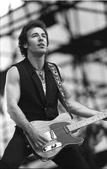 Black and white image of a man holding a guitar, wearing a dark vest and a cross hanging from a necklace