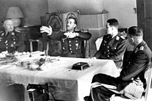 Black-and-white photograph of four men wearing uniforms sitting on wooden chairs around a table in a living room. An older man is sitting at the head of the table on the left. Two younger men are sitting along the table's side, with their backs towards a tiled fireplace on the room's far wall. A fourth man is sitting at the head of the table on the right, leaning back, his left leg folded over his right. The table is covered by a white table cloth. The right-hand side of the table is empty, except for a large dark ashtray, a spoon and an empty glass; the left and centre of the table is covered by an assortment of empty plates, coffee cups and other dishes; there is also a bowl of fruit. The second man from the left has his hands raised, palms facing the camera, and the fingers of both hands pointing to the left of the image. The heads of the three other men are turned towards him.