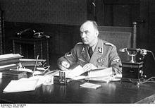Photographie montrant Arthur Greiser assis à son bureau, en uniforme, sans couvre-chef