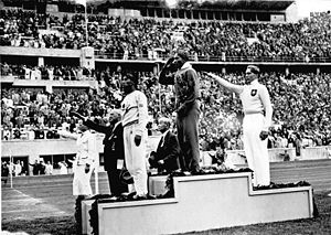 A black and white photograph of three men standing on a medal podium in front of a crowd at a stadium. The gold medallist is wearing a dark colored tracksuit and has his hand raised to his face giving a military salute, while the bronze medallist is wearing an all white tracksuit and is giving a Nazi style salute.