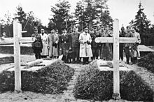 17 men, most in military uniform, stand in a cemetery, viewing two graves.