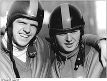 Two men wearing helmets embrace each other. The man on the left has his left arm over his partner's shoulder and grins while protecting his eyes from the direct sunlight with his brows.