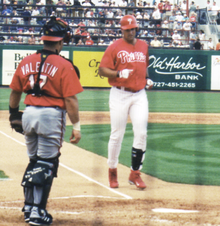 A man in a Philadelphia Phillies' uniform walking from third base to home plate