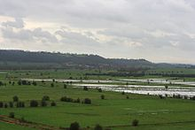 Water on grassy lowland with hills in the distance.