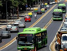 A green coloured Delhi Transport Corporation CNG bus in the middle of the road