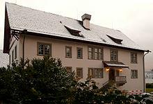 La maison abritant l'Institut C. G. Jung à Küsnacht. Il s'agit d'une petite maison vue de face, le toit recouvert de neige et tout autour de laquelle se trouvent des bosquets de conifères. La façade est légèrement de couleur rosée.