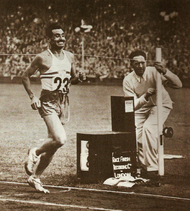 A black and white photo of a track athlete wearing the number 23 running.