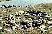 Photograph of a circular arrangement of rocks on open ground with a body of water in the background