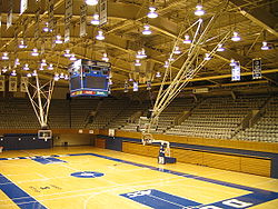 Interior of basketball stadium showcasing court, rafters, and empty stands