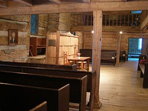 Photograph of the interior of an old log church with a rough hewn timber supporting column near the center of the image. The column supports a timber beam. Other beams are visible supporting a balcony that surrounds the room on three sides. The photograph is facing towards a communion table at the front of the church, and is taken from the left side of the room beneath the balcony. Plane wooden pews are visible to the left and on the other side of the room. The floor is wooden. A portrait of Thomas Campbell is visible to the left, on the front wall of the room.