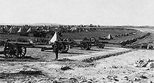 Foreground, a battery of 16 heavy guns. Background, conical tents and support vehicles.
