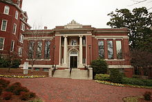 A one-story brick building with grey concrete stairs in the center leading to a door with a column on either side of it. There are three long windows on each side of the building.