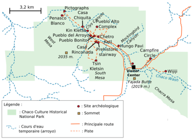 "A large green area representing Chaco Culture National Historical Park&squot;s boundaries sits in the middle of a white field. The green area is roughly rectangular with one smaller square-like and one triangular appendage abutting it at bottom-left and bottom-right, respectively. Fifteen small red circles represent the location of important Chacoan sites; they are focused on a line running from top-left (northwest) to bottom-right (southeast). A dashed blue line depicting the Chaco Wash runs roughly along the same line; a network of dashed and solid orange lines represent trails and metalled roads, respectively, also focus on the same axis, connecting the red dots. Two gold squares define high points: ""Fajada Butte (2019 m.)"" and ""West Mesa (2035 m.)""."