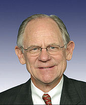 Upper body of a well-dressed, spectacled man with a receding hairline and graying hair. He is smiling.