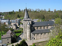 The houses of a small town, surrounded by green hillsides, are dominated by a huge church with a large square tower and a spire like a witch's hat.