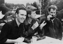 Three men are sitting at a small table. Man at left is holding sunglasses in his right hand, smiling, leaning forward and looking to his right. Man in middle has elbows on a brief case, gesturing with upraised hands, right hand is holding sunglasses, he is looking to his left. Third man has a small cup held to his lips by his right hand.