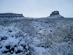 Rocky desert landscape blanketed in snow, shown in near-twilight. Two massifs, several miles in the distance, are snow-covered.