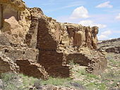 "Cliff-side set of ruined walls in daytime. In front of a cliff running diagonally from near left to middle right, rectangular slabs of stone, each somewhat smaller than a common brick, are stacked to compose a wall. Walls are seen delimiting several smallish rectangular ""rooms"". In the background at middle-right, a set of stone steps is seen leading up from the walls to the top of the cliff."