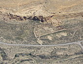 "Daytime birds-eye view of a desert with semicircular complex of ruined walls abutting a mesa, which covers the top third of the photo. The straight side of the complex faces a metaled road delimiting the bottom third of the image. The complex itself comprises many smaller enclosed circular and rectangular spaces. These ""rooms"" no longer have ceilings."