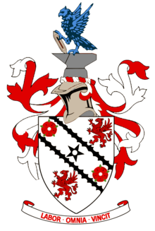 "A white shield upon which emblems of two red roses and two red griffins appear at alternate corners. A black five-pointed star is in the centre of the shield&squot;s design between two black diagonal lines. Around the shield are red and white ribbons in a symmetrical design. Above the shield is a silver-coloured knight&squot;s helmet surmounted by grey anvil upon which a vivid azure-coloured eagle is perched, holding a grey shuttle. Below the shield is the motto ""LABOR OMNIA VINCIT""."