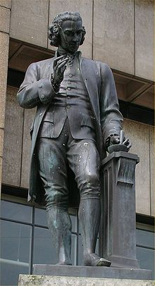 Statue of a man with a mortar and pestle in his left hand and his right-hand upraised.