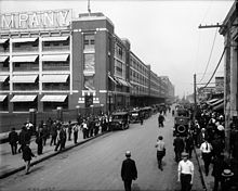 Masses of men throng the streets outside a building.