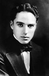 The black-and-white portrait of a young man. He is looking forward. He is wearing a black tux and a black bow tie.