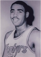 "A man, wearing white basketball jersey with the word ""ZEPHYRS"" on the front, is posing for a photo."