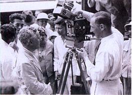Henk Alsem, in de vooroorlogse jaren een bekende Nederlandse film- en documentairemaker. Charlie Chaplin bewondert Henk Alsems 35 mm cinecamera op Tanjung Priok Wharf nadat de komiek in de haven van Batavia (later Jakarta) was aangekomen. Chaplin was zelf een verwoed amateurfilmer en hij had zijn eigen 16 mm cinecamera. (1931)