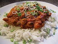 A dish of rice (white) with Kadai chicken (dark orange) on it in a plate