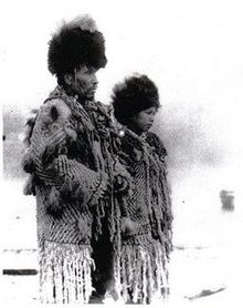 """Black and white photograph of Skwxwu7mesh Chief George from the village of Senakw with his daughter in traditional regalia."""