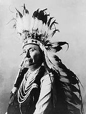 Profile of the head and torso of a dignified man of about age 60. He wears a headpiece featuring many long white feathers with black tips. His shirt or upper garment is dark, though its sleeves are white. Decorative parallel ovals of a white material extend down the front of this garment from neck to midriff.