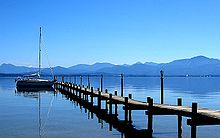 Image of a pier extending out in to a lake, with a clear sky above and mountains in the distance.