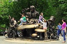 grande sculpture en bronze avec personnages et champigons