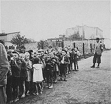 La photographie montre un groupe d'enfants du ghetto de Lodz en rangs le long d'une clôture grillagée, en attente de leur déportation au camp de Chelmno.