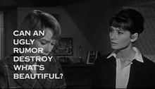 "Still shot of a film trailer showing Shirley MacLaine looking down at the left and Audrey Hepburn to her right staring at her, in a bedroom. The words ""Can an ugly rumor destroy what&squot;s beautiful?"" obscure much of MacLaine&squot;s face"