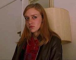 Photo of a young strawberry-blonde woman with a look of confusion on her face; she is clad in a brown leather jacket and pink t-shirt.