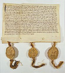 Picture of a deed which has hand-written writing on a yellowed piece of paper with three gold tassles at the bottom