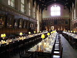 interior of large mediaeval building with tables and benches