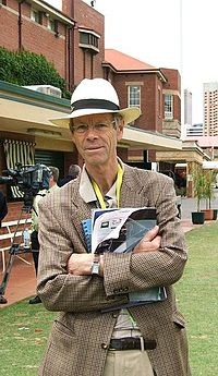 A man in a tweed jacket and a wide-brimmed hat, with his arms crossed holding some papers