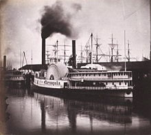 Black and white photo of a pair of steamboats moored at a dock; smoke is issuing from one of the boat's funnels; the masts of several sailing ships are visible in the background