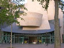 Photographie de l'entrée de la Cinémathèque française, dont on voit les portes coulissantes ouvertes